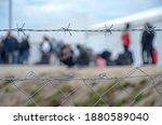 Small photo of Barbed wire in refugee camp. Migrants behind chain link fence in camp. Group of people behind fence. Concept of prison, freedom, barrier, security and migration. Refugees on their way to EU.