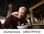 Small photo of Disgusted young man found hair in his meal at cafe and looks at it with loathing. Bad customer service concept. Blond young man in casual clothes isn't satisfied with the food.