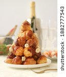 Small photo of A traditional French croquembouche or piece montee, with flute and champagne in background. It's a French dessert consisting of choux pastry puffs piled into a cone and bound with threads of caramel