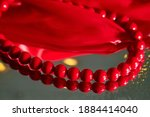 Red Beads Lying On Mirror And...