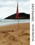Red Flag Waving On The Sand A...