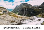Trollstigen, Andalsnes, Norway. Bus Goes On Road Near Stigfossen Waterfall. Famous Mountain Road Trollstigen. Norwegian Landmark And Popular Destination. Norwegian County Road 63 In Sunny Summer Day. - stock photo