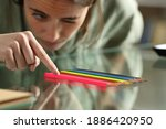Small photo of Obsessive compulsive woman aligning up pencils accurately on a glass table