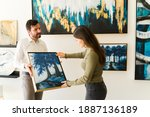Small photo of Male artist showing his painting to a female client interested in buying some artwork from the exihibiton of the art gallery