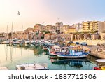 View to Heraklion in the early morning during sun rise, the old port with traditional fishing boats and town with its antient buildings at the background. Selective focus