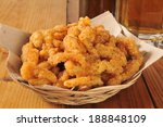 A basked of deep fried breaded clam strips with a mug of beer