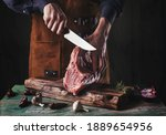 Small photo of A guy in a leather apron is slicing raw meat. The butcher cuts the pork ribs. Meat with bone on a wooden cutting board.
