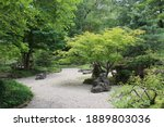 A white crushed stone path through a tree filled garden with varying shades of green foliage in Janesville, Wisconsin, USA