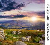 mountain landscape. valley with stones on the hillside. forest on the mountain under the beam of light falls on a clearing at the top of the hill. at sunset - stock photo