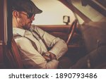 Retro Looking Caucasian Men in His 30s Seating Inside His Classic Car. Transportation and Lifestyle Concept. - stock photo