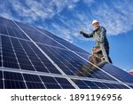 Small photo of Low angle view portrait of a smiling worker, installing solar batteries, who is standing on ladder at solar plant against blue sky, showing thumb up. Concept of alternative sources of energy.