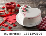 Small photo of Heart cake for St. Valentine's Day, Mother's Day, or Birthday, decorated with roses and pink sugar hearts on wooden table