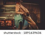 Thirty Seven Years Old Cowboy Wearing Leather Western Style Hat and Gloves and His Classic Vintage Car. Automotive Theme. - stock photo