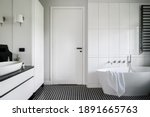 Small photo of Luxury black and white bathroom with freestanding bathtub, stylish mosaic tile floor and white doors with black handle