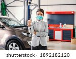 Small photo of Smiling, friendly female car seller with face mask standing in garage of car salon and showing thumbs up. Car is all set and repaired.