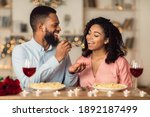 Small photo of Affectionate young black couple having dinner, guy feeding his girlfriend with pasta. Cute lovers having romantic date, flirting, having fun, celebrating St Valentine's Day or holiday