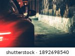 Automotive Concept. Modern Luxury Car In the Dark City Alley During Late Night Hours. Vehicle Rear Lights. - stock photo