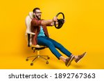 Small photo of Full length body photo of playful crazy man in chair holding steering wheel pretending car rider isolated vivid yellow color background