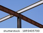 Small photo of Steel beams and girder prepared supporting underneath roof of building at construction site. Blue sky background. Concept of steel beams, girder, construction site.