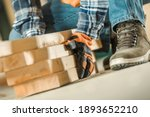 Lumber Worker Moving Wood Beams Using Working Place Safety Gloves Close Up. Building Wooden Skeleton Frame. - stock photo