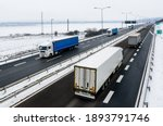 Highway transportation with a convoy of Lorry trucks passing trucks in a snowy winter landscape