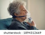 Small photo of Ill senior woman making inhalation at home. Close up of an elderly woman holding mask nebulizer inhaling fumes medication into lungs. Self treatment of the respiratory tract using inhalation nebulizer
