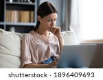 Small photo of Close up thoughtful upset woman looking at laptop screen, pondering ideas or difficult tasks, sitting on couch at home, pensive young female touching chin, reading news, waiting for message
