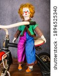 Small photo of Chambersburg,Pennsylvania,USA 1-17-2021 child's vintage clown doll sitting on old metal tricycle