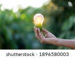 Hand Holding Light Bulb Energy...