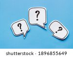 Small photo of Question mark on paper bubbles, top view. Question concept