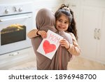 Small photo of Smiling little girl holding greeting card for Happy Mother's Day with drawn red heart and hugging her muslim mom. Loving islamic family bonding together at home, closeup shot with free space