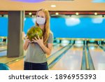 Woman playing bowling with...
