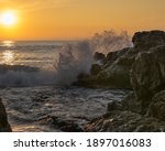 Wave Crashing On The Rocks At...