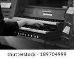 Small photo of Hands of a woman playing the organ in black and white