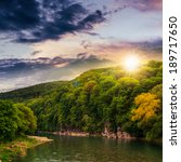 calm river flowing between green mountains on a cloudy summer sunset - stock photo