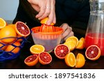 Small photo of A man squeezes orange juice into a juicer from Tunisian oranges. A basket of oranges, halved oranges, orange peels and a decanter of orange juice next to the juicer.