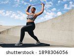 Small photo of Full length of plus size woman exercising with resistance band. Female doing resistance band workout outdoors in morning.