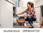 Small photo of Diligent housewife putting dishes into dishwasher.