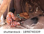 Small photo of Moroccan local nomadic bedouin family live in nomad tent camp in native berber tradition in african Sahara desert and prepare traditional turkish flatbread in hot oven near Merzouga, Morocco, Africa.