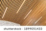 Small photo of Loft style wooden plank ceiling design idea. Slatted wooden ceiling in the interior. Designer ceiling close-up. LED strip lamps in the design of a wooden ceiling.