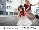 Small photo of Horizontal outdoor image of a happy little girl playing hopscotch with her mother on playground outdoors. Child plays with her mom oustside. Kid plays hopscotch drawn on pavement. Activities and games