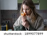 Small photo of Sick woman trying to sense smell of fresh tangerine orange, has symptoms of Covid-19, corona virus infection - loss of smell and taste, standing at home. One of the main signs of the disease.