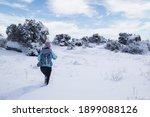 A Woman Walks Through Snow...