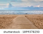 Sandy beach on sunny day with wooden walkway