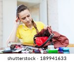 Small photo of inconsiderate woman lost something and finding in handbag