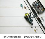Small photo of Fishing tackles lay on white wooden boards. Set of fishing tackles. Top view on spool, rod, spoons, wobblers and lure box.