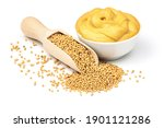 Mustard seeds in the wooden scoop and mustard sauce in the bowl isolated on white background.