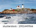Wave splashes near Cape Neddick (Nubble) lighthouse in Maine. The lighthouse sits atop a tiny rocky island and is a famous photographic tourist attraction.