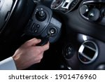 Small photo of Close-up of a male hand putting an ignition key into an ignition. Starting a car engine, a vehicle.