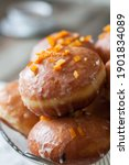 Small photo of Traditional polish donuts - paczki. Deep fried yeast buns filled with marmalade, covered in icing